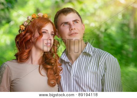 Portrait of nice dreamy couple spending time together in fresh green spring park, with interest looking up in the sky, love and romantic relationship concept