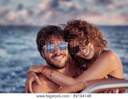 Closeup portrait of cheerful happy lovers on sailboat, young couple having fun in romantic sea traveling, love concept
