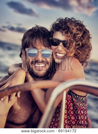 Closeup portrait of cheerful happy lovers on sailboat, young couple having fun in romantic sea traveling, love and enjoyment concept