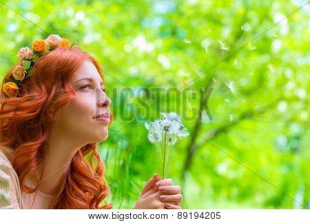 Closeup portrait of nice happy woman holding in hands dandelion flowers, having fun in fresh green park, enjoying beauty of spring nature