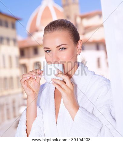 Portrait of a beautiful woman having morning tea in hotel room in Florence, Italy, Europe, standing on the balcony over  wonderful cityscape background