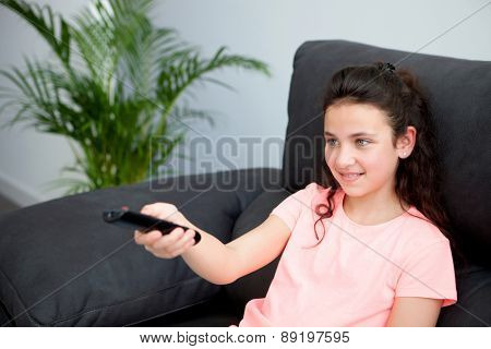Young girl with a remote control on her sofa at home