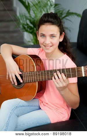 Young girl playing a guitar on the sofa at home