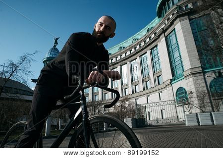 bald bearded guy on black fix against semicircular building
