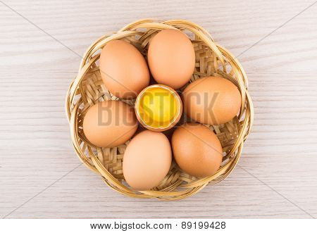 Chicken Eggs In Basket With One Broken Egg