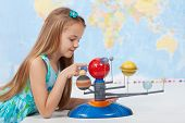 picture of geography  - Little girl studies the solar system in geography class  - JPG