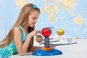 picture of earth mars jupiter saturn uranus  - Little girl studies the solar system in geography class  - JPG