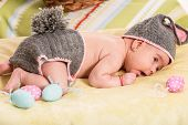 foto of baby easter  - Newborn baby girl in crochet bunny costume with Easter eggs - JPG