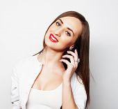 stock photo of long distance relationship  - Pretty young woman using mobile phone over white background - JPG