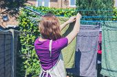 picture of laundry  - A young woman is hanging her laundry on a clothes line in the garden on a sunny day - JPG