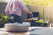 pic of braai  - Stack of plates on a table outside in a garden with a man attending to a barbecue in the background - JPG