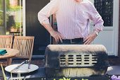 stock photo of braai  - A senior man is attending to a barbecue in the garden on a sunny day - JPG