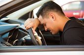 image of upset  - Profile view of a young man leaning on the steering wheel and feeling stressed and upset - JPG