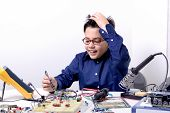stock photo of experiments  - Young student performs experiments in electronics and dreams of the future - JPG
