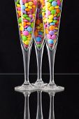 foto of champagne color  - Color chocolate tablets inside the champagne glasses on a black glass plate - JPG