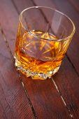 stock photo of tumbler  - Tumbler glass full of whisky standing on a wooden table - JPG