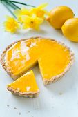 pic of tarts  - Tasty homemade sweet fruit tart pie with lemon cream filling with narcissus flowers on white table - JPG