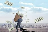 picture of heavy bag  - Businessman carrying bag of dollars against cracked balcony overlooking city - JPG