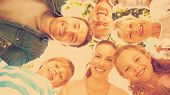 image of huddle  - Low angle portrait of an extended family forming huddle in the park - JPG