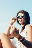 foto of rude  - Fashion outdoor portrait of young beautiful sensual woman in summer having fun sitting on the street in sunglasses in evening sunset Girl showing rude gesture - JPG