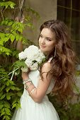 foto of fascinator  - Beautiful smiling bride with wedding bouquet of flowers at park - JPG