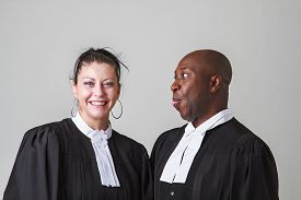 image of toga  - bald black man making a face to a woman both wearing canadian lawyer toga - JPG
