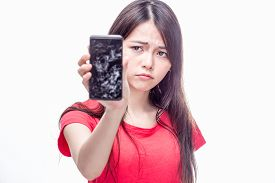 image of frown  - Frowning Chinese woman holding cell phone with cracked screen - JPG