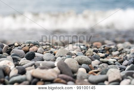 pebbles on the beach with a wave. Shallow focus