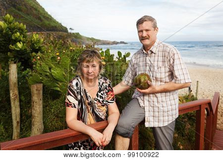 Couple Man And Woman Smiling And Holding Coconut On Beach