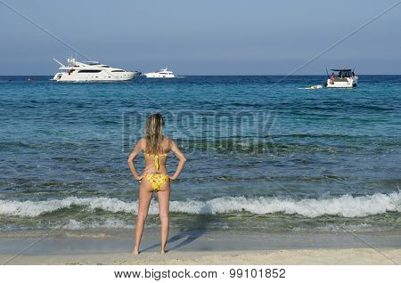 Girl Looks Speedboats From The Beach