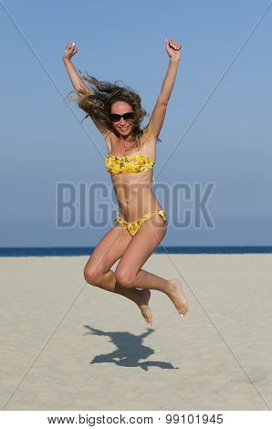 Girl Jumps Up On The Beach