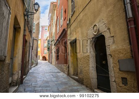 Narrow cobblestone street in medieval town Villefranche-sur-Mer on French Riviera, France.