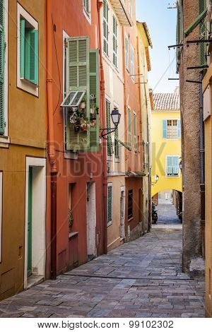Row of colourful old buildings with bright window shutters along cobblestone street in medieval town Villefranche-sur-Mer on French Riviera, France.