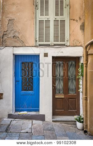 Two doors and window with shutters on old house in Villefranche-sur-Mer, France.