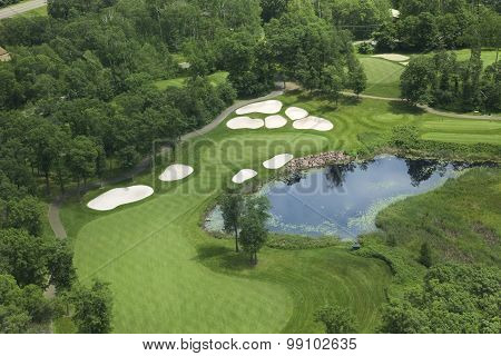 Aerial View Of Golf Fairway And Green With Traps, Pond And Trees