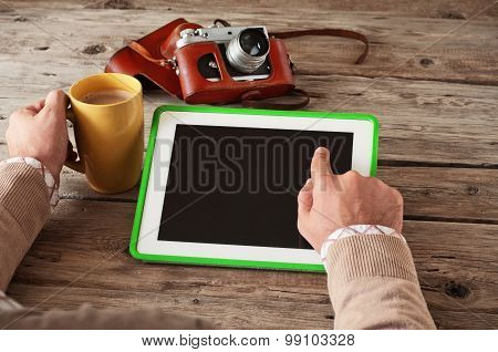 Male hand clicks then blank screen tablet computer on the wooden table and holding a cup of coffee c