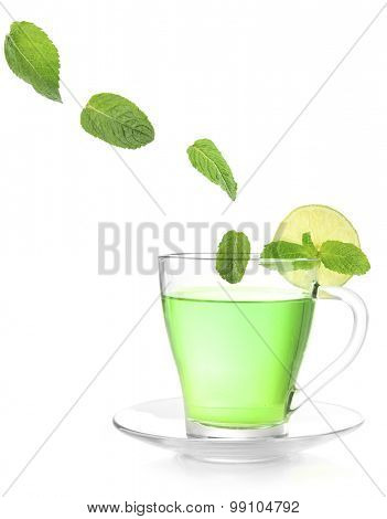 Mint leaves falling in cup of green tea isolated on white