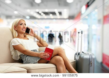 Business woman with suitcase in hall of airport