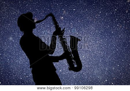 Saxophonist. Woman playing on saxophone against the background of starry sky