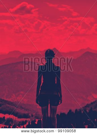 Artistic dramatic toned portrait of a silhouetted woman enjoying a dramatic red sunset from a mountain peak looking out over mountains and valleys