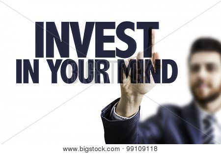 Business man pointing the text: Invest In Your Mind