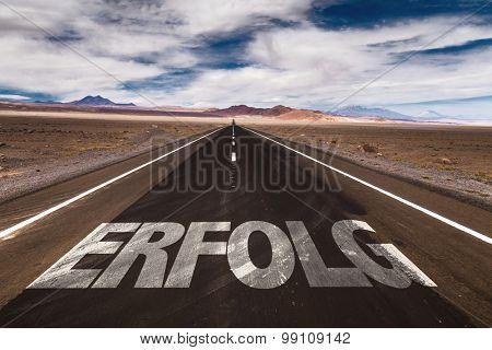 Success (in German) written on desert road