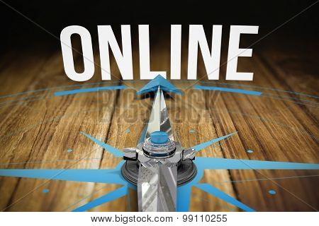 The word online and compass against wooden table