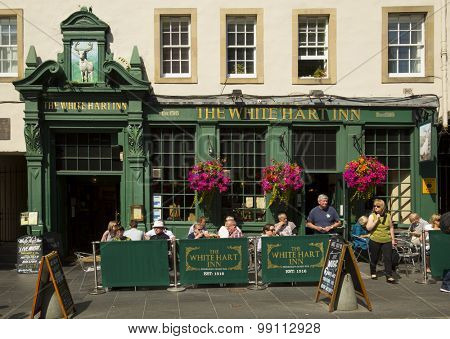 EDINBURGH - AUGUST 17, 2015:  People having food and drink in a classical pub in Edinburgh, Scotland.  In many places, especially in villages, a pub can be the focal point of the community.