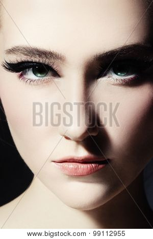 Close-up portrait of young beautiful girl with fancy cat eye make-up
