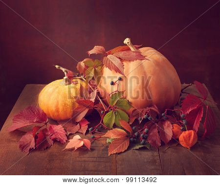 Autumn still life - pumpkins, autumn leaves  and physalis against the background of old wooden wall. Toned image.