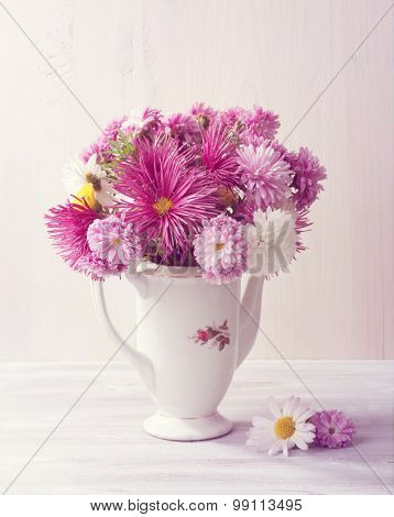 Still life with colourful chrysanthemums bunch on  white wooden board. Toned image