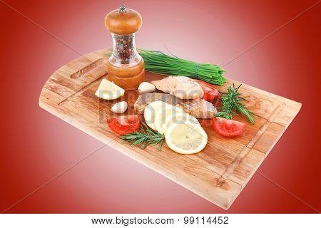 savory fish portion : grilled norwegian salmon fillet with green chinese onion, red cherry tomatoes , allspice pepper in grinder, rosemary twigs lemon slice wooden board isolated over white background