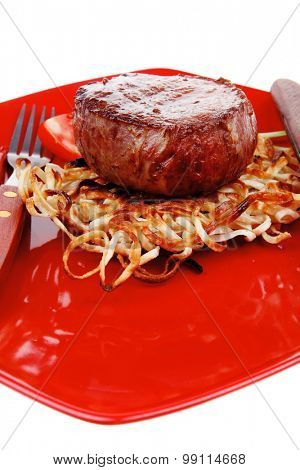 grilled beef fillet medallions on noodles and red hot chili pepper on red plate isolated over white background