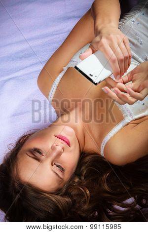 Lying Girl Holding Smartphone.